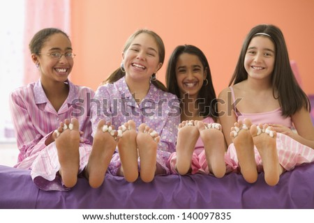 Four girls sitting on bed with bare feet - stock photo