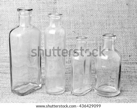 Four glass bottles in black and white
