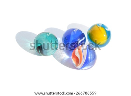 Four glass marbles on white background - stock photo