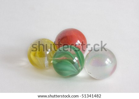 Four glass marbles, transparent, green, yellow and red. - stock photo