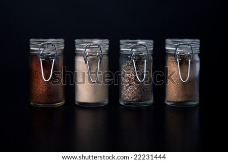 Four glass spice jars lined up in a row against a black background. - stock photo