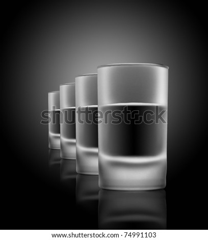 Four glasses of beverage on a glass table