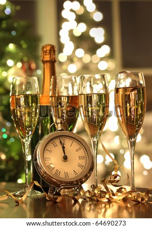 Four glasses of champagne ready for the countdown to the New Year - stock photo