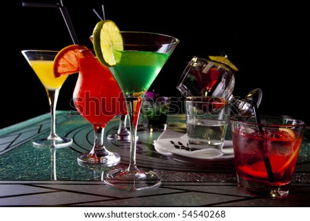 Four glasses of colorful cocktails in dark - stock photo