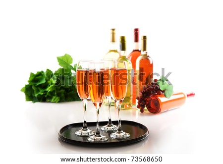 Four glasses of pink sparkling wine and wine bottles - stock photo