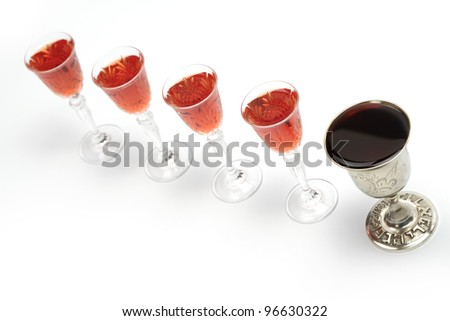 Four glasses of wine and one silver cup for Passover seder.Isolated