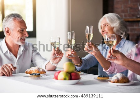 Four glasses of wine being raised at the house party