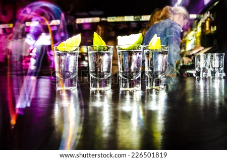 four glasses with Lim on the bar at a nightclub - stock photo
