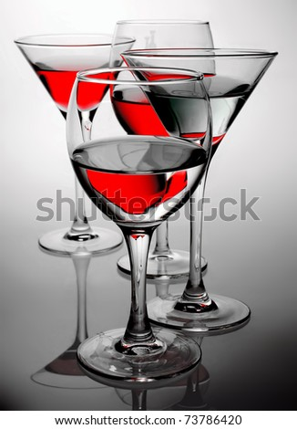 four glasses with red wine and blue liquor against a gradient from white to the black