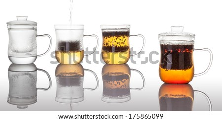 Four glasses with the leaves of red tea prepared with boiled water on the white background with reflection