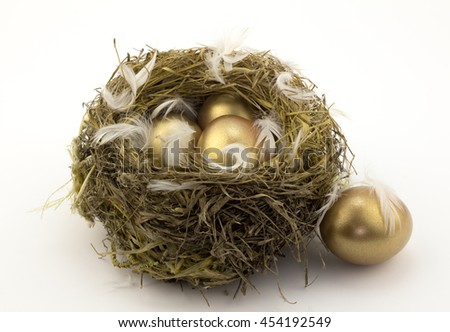 Four gold nest eggs isolated on white - stock photo
