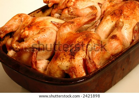 Four golden brown cornish game hens in a stone baking dish on a white background. - stock photo