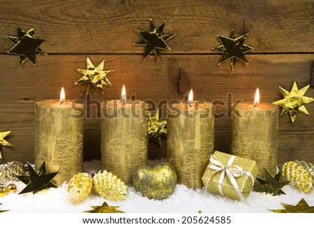 Four golden burning christmas candles for advent decoration. - stock photo