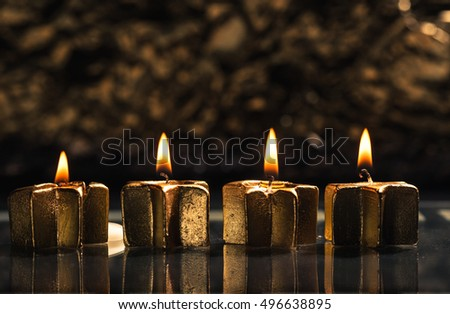 Four golden candles lit for fourth advent, shallow depth of field with reflection and bokeh light background.
