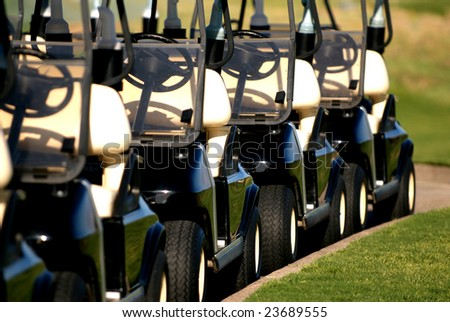 four golf carts in a row from front view - stock photo