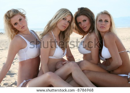 Four gorgeous bikini models at the beach - stock photo