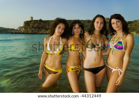 Four gorgeous young girls relaxing by the ocean during a hot summers day in Malta in their bikinis.