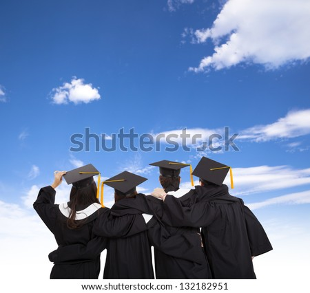 four graduate students looking at sky - stock photo