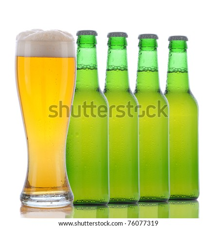 Four Green Beer Bottles and a Full Glass of ale on a white background. Square format with bottles arranged in a line behind the glass.