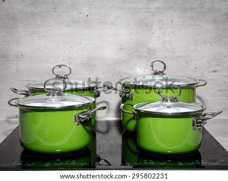 Four green enamel stewpots on black induction cooker - stock photo