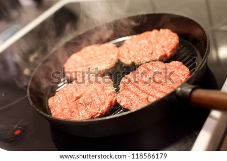 Four hamburgers in a hot frying pan. - stock photo