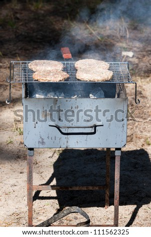 Four Hamburgers on Barbecue Grill - stock photo
