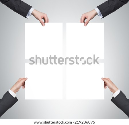 Four hands are holding four empty posters. - stock photo