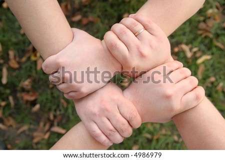 four hands hold each other - stock photo