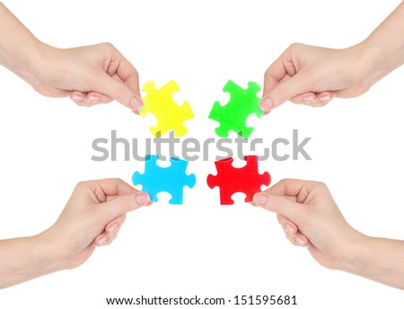 Four hands holding colorful puzzle, isolated on white