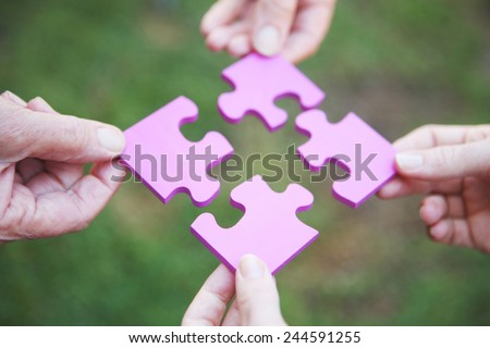 Four hands holding pieces of a pink jigsaw puzzle - stock photo