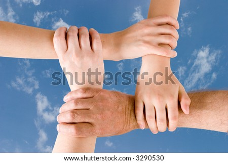 Four hands joined together - stock photo