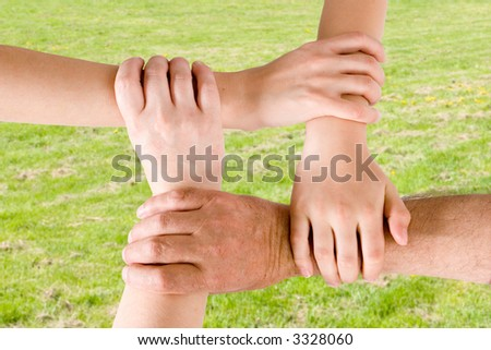 Four hands joined together with a grass background - stock photo