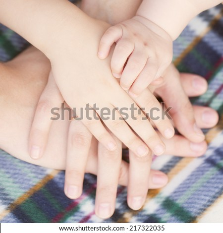 Four hands of the family, baby, child, mother and father together.  - stock photo