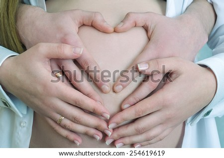 Four hands on a pregnant belly, close-up, Heart Shaped Pregnancy Portrait - stock photo