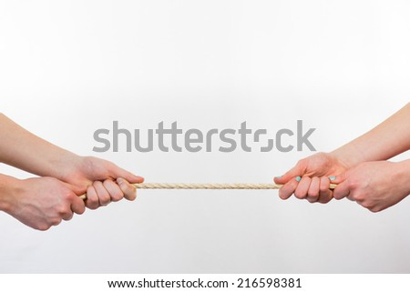 Four hands pulling rope as contest - stock photo