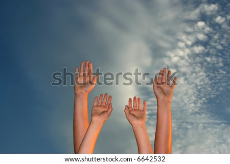 four hands raised to sky at sunset - symbol of friendship, partnership, teamwork