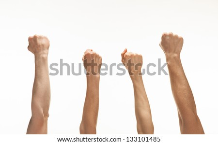Four hands showing fists raised up, white background - stock photo