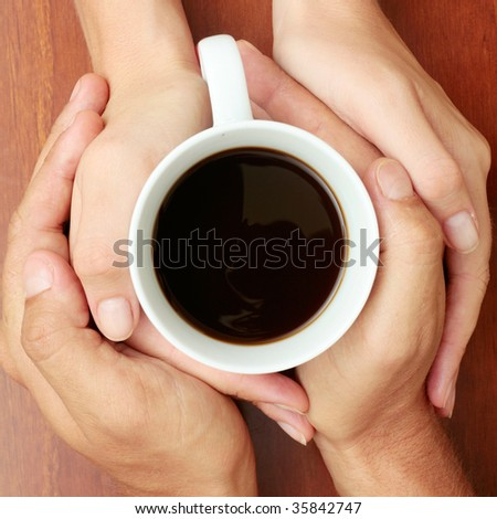 Four hands wrapped around a cup of coffee - stock photo