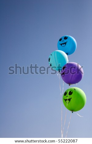 Four happy balloons with smile in cyan sky