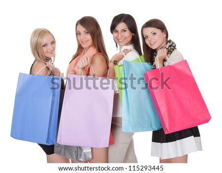 Four happy beautiful female shoppers carrying colorful shopping bags isolated on white - stock photo