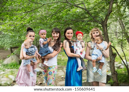 Four Happy Beautiful Mothers and children hugging and laughing. The concept of childhood and family. - stock photo