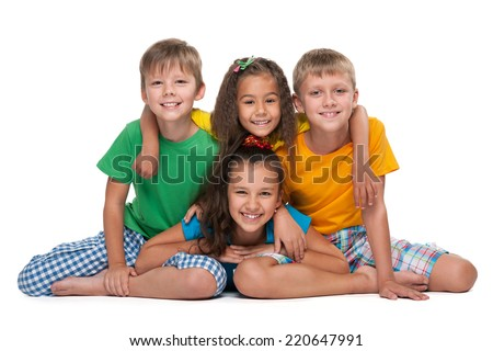 Four happy children sit on the white background - stock photo