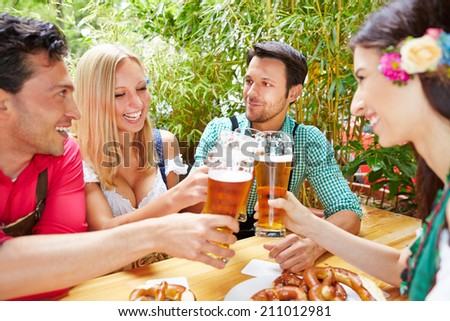 Four happy friends clinking glasses with beer at Oktoberfest - stock photo