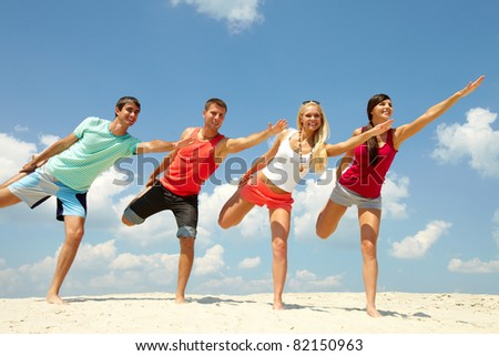 Four happy friends doing exercise on the beach