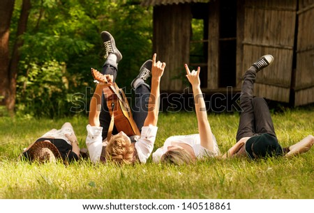 Four happy friends relax with guitar music on the green meadow - stock photo