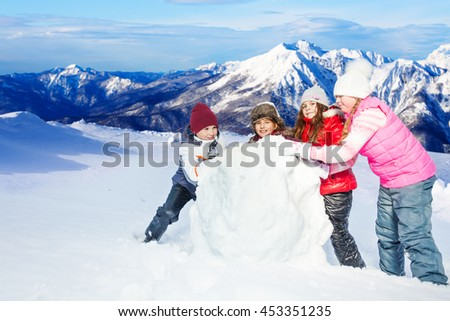 Four happy friends rolling the snowball at winter