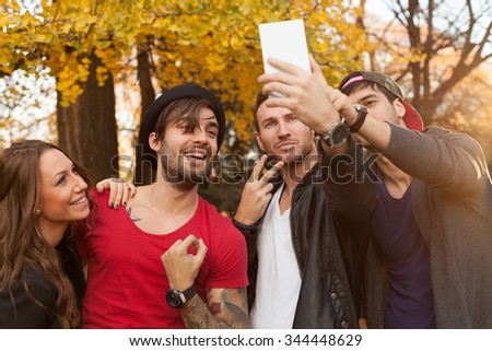 Four happy friends smiling and taking a selfie. - stock photo