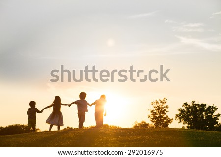 Four happy kids are playing on sunset. They jumping and holding by hands.
