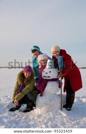 Four happy ladies with snowman at the wintry field - stock photo