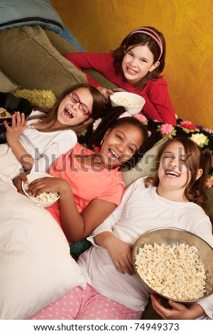 Four happy little girls on a couch eat popcorn - stock photo